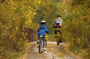 family in fall riding bikes